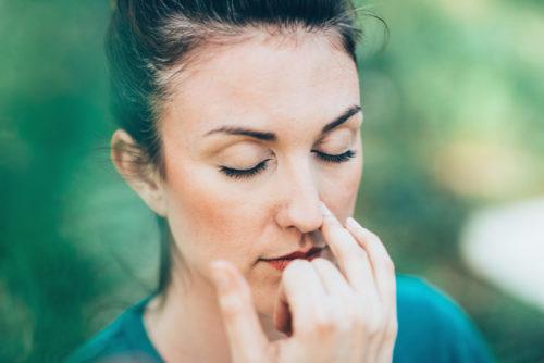 Frau führt Atemübungen aus. Pranayama hilft dir ruhiger werden.